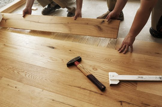 Two men laying finished parquet flooring, close-up